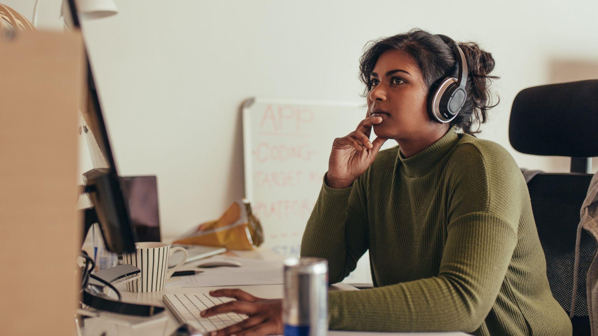 Jeune femme qui porte un casque audio et qui travaille à l'ordinateur